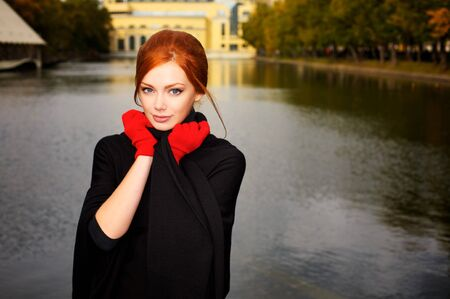 Portrait of a beautiful red-haired woman in red gloves Stock Photo