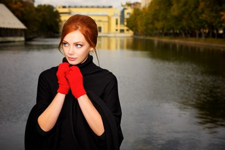 outdoor glamour: Portrait of a beautiful red-haired woman in red gloves Stock Photo