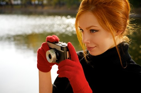 Portrait of a beautiful red-haired girl in red gloves with a camera