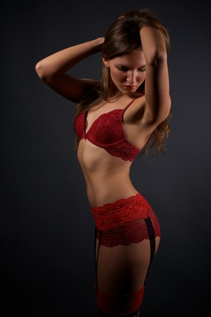 Pretty young woman in red lingerie and stockings standing in the studio photo