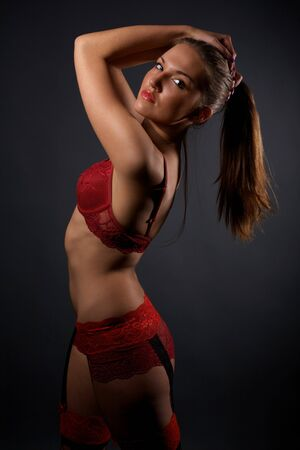 Beautiful young woman in red lingerie and stockings standing in the studio photo