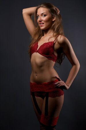 black stockings: Pretty young woman in red lingerie and stockings standing in the studio