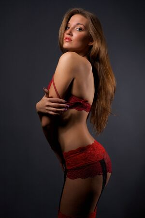 garter: Pretty young woman in red lingerie and stockings standing in the studio