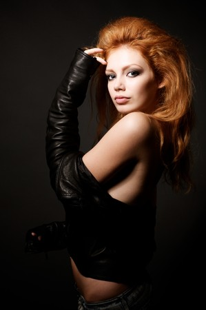 Portrait of beautiful young redhead woman over dark background Stock Photo