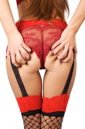 Buttocks of young beautiful woman in red sexy panties and stockings over white background