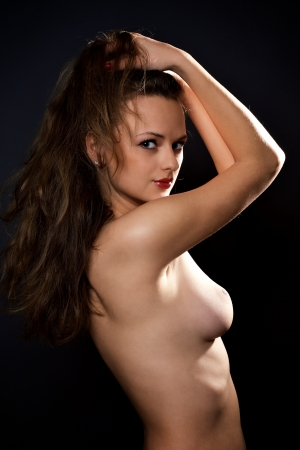joven desnudo: Retrato de joven desnuda sobre estudio oscuro, disparo Foto de archivo