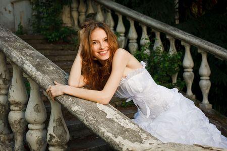 robe de soir�e: Promise posant dans les escaliers de vieux abandonn� maison  Banque d'images