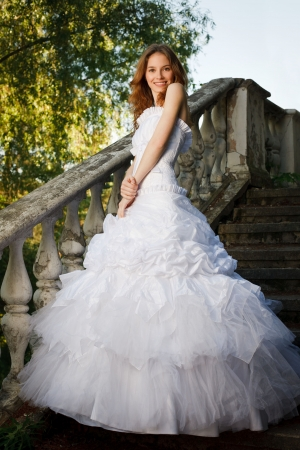 Bride posing on stairs of old abandoned house photo