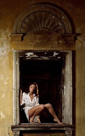 Sexy woman posing in window of old ruined house Stock Photo - 7274577
