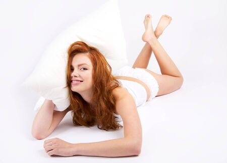 Portrait of lovely redheaded woman with pillow on white photo