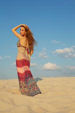 Beautiful woman posing on sand photo