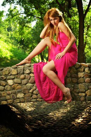 Young beautiful girl on a stone bridge photo