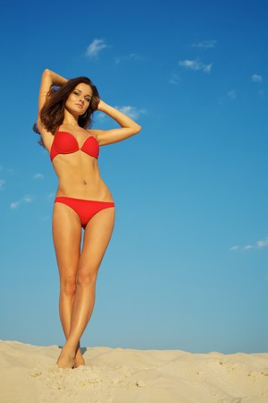 Beautiful young woman in red swimsuit posing on sand