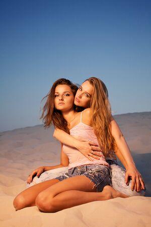 Two sexy girls posing in desert photo