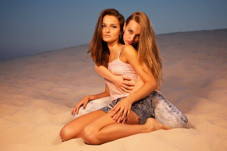 Two sexy girls posing in desert photo
