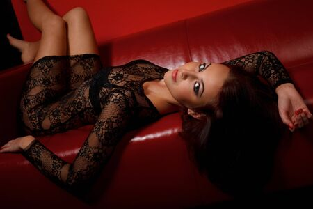 Young woman in black dress lying on red sofa