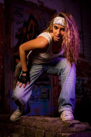 street dance: Young woman dancer on graffiti background