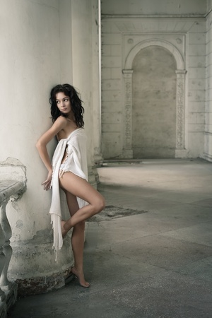 column arch: Beautiful sexy woman posing in a castle interior