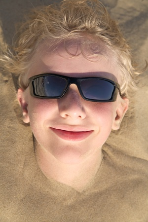 bury: Young boy relaxing on summer beach in sunglasses