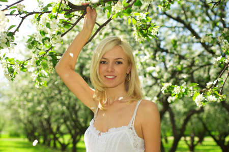 Young beautiful woman in a white dress in blooming gardens Stock Photo - 9267714