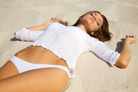 Young beautiful sexy tanned woman laying on sea beach