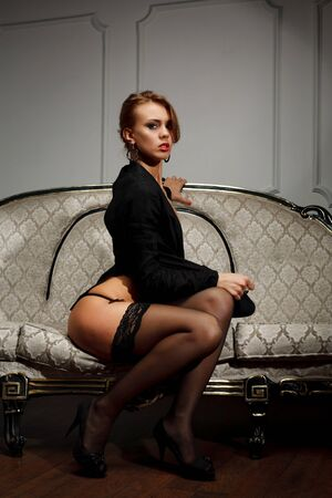 Young woman in black lingerie  sits on the couch