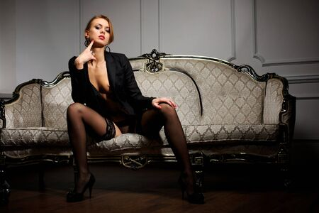 Young woman in black lingerie sitting on the couch Stock Photo