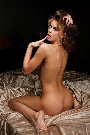 Studio portrait of attractive sexy woman in bed