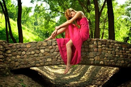 Young beautiful girl sitting on a stone bridge photo