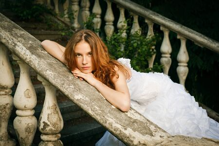 abandon: Bride posing on stairs of old abandoned house