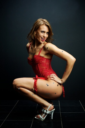 Attractive young woman in red lingerie on a dark background Stock Photo - 9861286