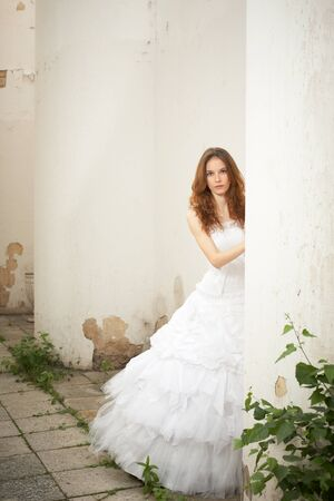 Beautiful young bride looks out for the old column Stock Photo - 9843886