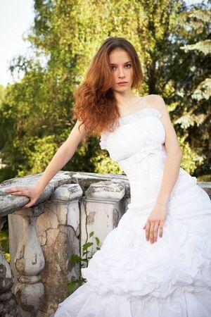Bride posant sur les marches de la maison abandonnée ancienne