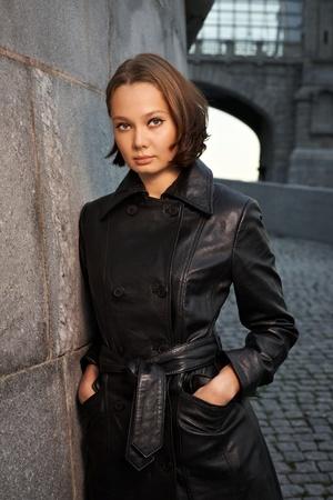 Beautiful young woman near stone wall photo