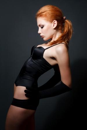Attractive redhead woman posing on studio dark background