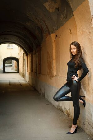 Young beautiful female model standing near old wall Stock Photo