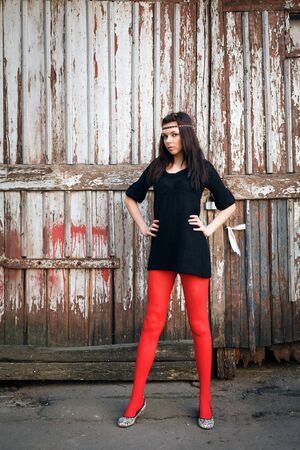 Young beautiful woman against the backdrop of an old barn photo
