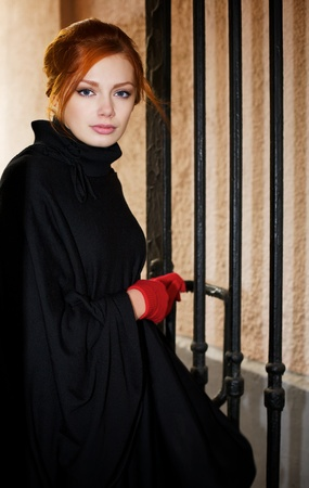 Young beautiful woman next to the gate photo