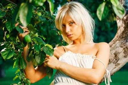 Young beautiful blonde woman near apple tree Stock Photo - 10056760
