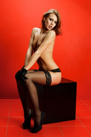 Attractive young topless woman sitting on black cube