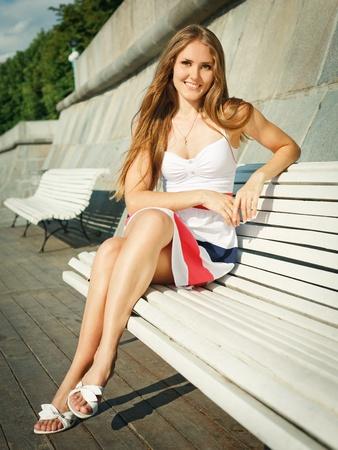 Young beautiful woman sitting outdoors Stock Photo