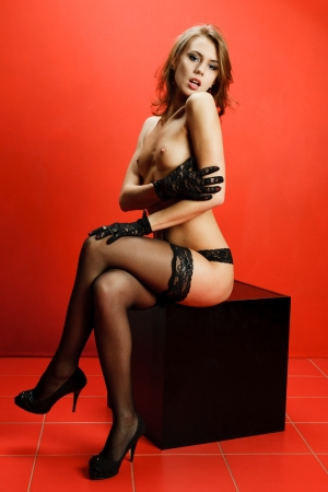 Attractive young topless woman sitting on a black cube with a red background