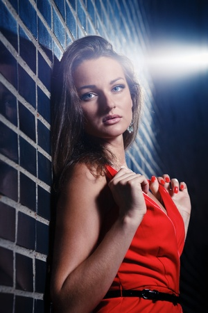 Beautiful young woman in a red dress at night photo
