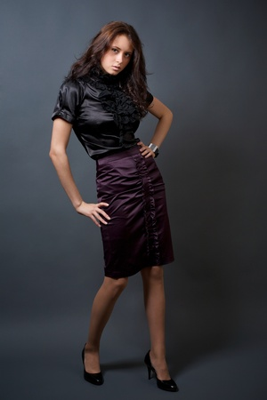 Portrait of attractive young model in a skirt on a dark background Stock Photo
