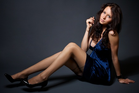 Portrait of attractive young model in a blue dress on a dark background