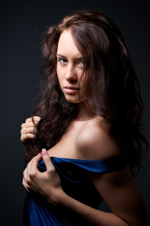 Portrait of attractive young model in a blue dress on a dark background Stock Photo - 11980218