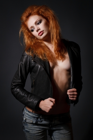 Portrait of a beautiful young redhead woman in a leather jacket photo