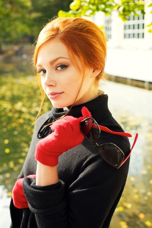 redheaded: Portrait of a beautiful red-haired woman in red gloves Stock Photo