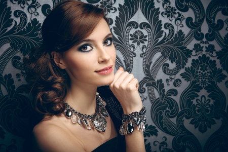 Portrait of pretty young woman with beads and bangle photo