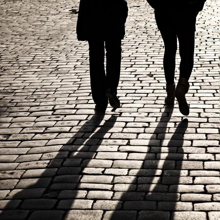 shadows: Sombras de personas caminando en una calle de la ciudad